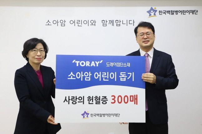 김은주 도레이첨단소재 상무(왼쪽)가 11일 서선원 한국백혈병어린이재단 사무총장에게 헌혈증 300매를 전달한 뒤 기념촬영을 하고 있다.ⓒ도레이첨단소재