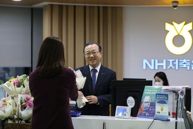 김건영 NH저축은행 대표이사(사진 가운데)가 14일 서울 강남구 소재 은행 본점영업부를 찾은 고객에게 직접 꽃을 나눠주고 있다.ⓒNH저축은행