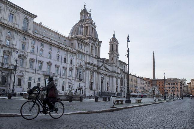 신종 코로나바이러스의 급한 확산으로 이동금지령이 내려진 채 텅빈 이탈리아 로마 시내 중심가의 나보나 광장을 12일(현지시간) 한 여성이 자전거를 타고 지나가고 있다.ⓒ뉴시스