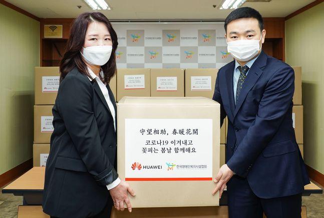 멍 샤오윈 한국화웨이 CEO(오른쪽)이 정은영 한국장애인복지시설협회 부회장에게 마스크를 전달하고 있다.ⓒ화웨이