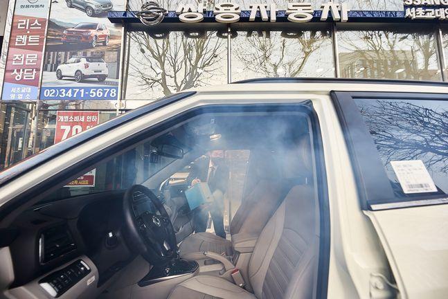 쌍용차 영업사원이 전시장을 방문한 고객 차량에 항균 연막소독을 하고 있다. ⓒ쌍용자동차