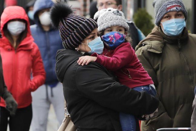 미 매사추세츠주 첼시에서 코로나19 확산 예방을 위해 마스크를 쓴 한 모녀가 수백 명의 주민과 함께 기부 음식을 받기 위해 줄 서 있다(자료사진). ⓒAP/뉴시스