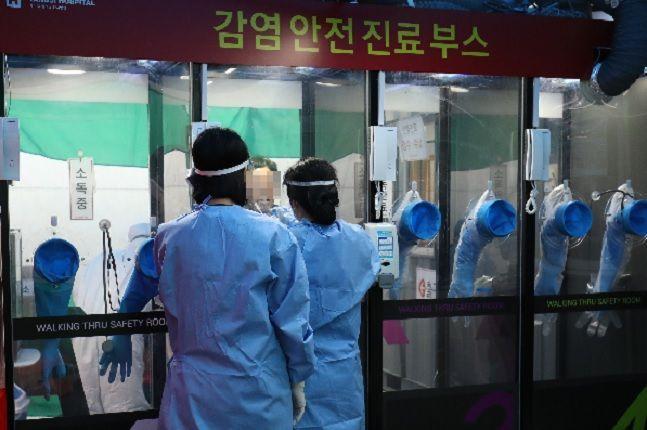 서울 관악구 에이치플러스 양지병원에서 의료진들이 공중전화 박스 형태의 코로나19 감염 안전 진료 부스를 이용해 검사 대상자를 검진하고 있다(자료사진). ⓒ데일리안 류영주 기자