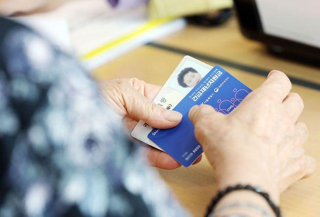 코로나19 대응을 위한 긴급재난지원금 현장 신청 첫 날 주민센터에서 한 주민이 선불카드를 들고 있다. ⓒ뉴시스
