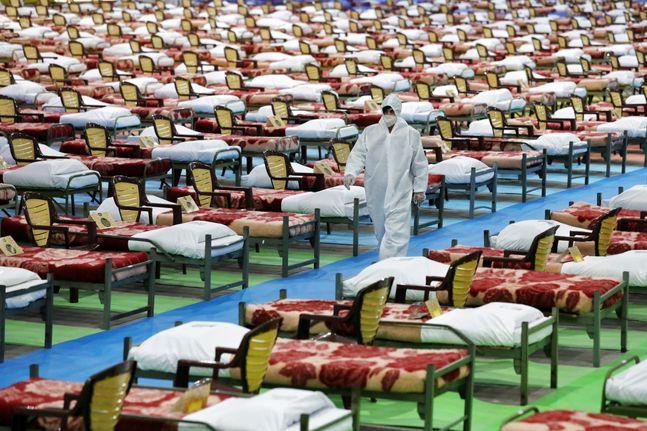 지난 3월 26일(현지시간) 이란 수도 테헤란의 한 임시병원에서 보호복을 입은 한 관계자가 침대 사이를 걸어가고 있다. 이란군은 신종 코로나바이러스 감염증(코로나19) 환자를 수용하기 위해 국제전시관을 2000개 병상 규모의 임시 병원으로 개조했다.ⓒAP/뉴시스