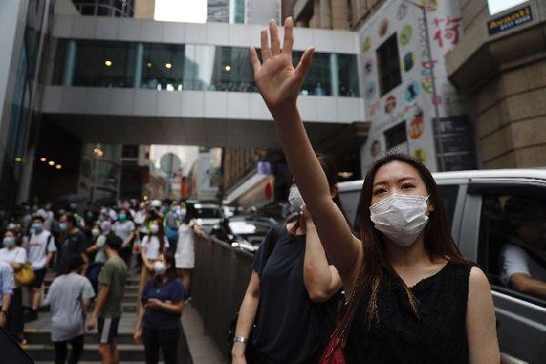 27일 홍콩 입법부 앞에서 한 여성이 다섯 가지 요구사항을 의미하는 손가락을 펴 보이며 시위에 참여하고 있다. ⓒ홍콩=AP/뉴시스