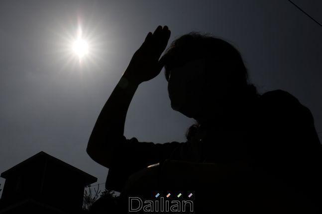 서울 종로구의 한 거리에서 시민이 햇빛을 손으로 가리며 이동하고 있다. ⓒ데일리안 류영주 기자