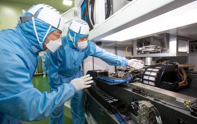삼성전자 한 직원(왼쪽)이 협력사 이오테크닉스 직원(우)과 양사가 공동 개발한 반도체 레이저 설비를 함께 살펴보고 있다.ⓒ삼성전자