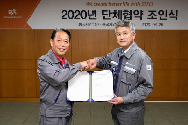 장세욱 동국제강 부회장(오른쪽) 과 박상규 노조위원장이 합의서를 들고 주먹 인사를 나누고 있다.ⓒ동국제강