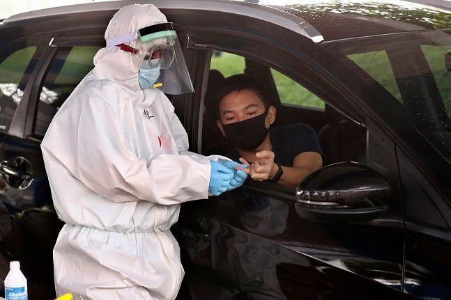 인도네시아 탕에랑의 차량 탑승 검사소에서 한 의료관계자가 신종 코로나바이러스 감염증(코로나19)의 항체 검사를 위해 한 남성의 혈액 표본을 채취하고 있다.ⓒ뉴시스