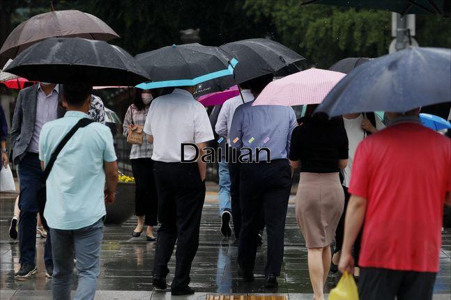 지난 24일 오후 서울 종로구 광화문 거리에서 우산을 쓴 시민들이 내리는 장맛비 속에서 발걸음을 옮기고 있다. ⓒ데일리안 홍금표 기자