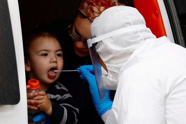 이스라엘 텔아비브 교외 초정통파 유대교 도시인 브네이 브락에서 한 유대인 소년이 보호장구를 착용한 의료진으로부터 코로나19 검사를 받고 있다.ⓒ뉴시스