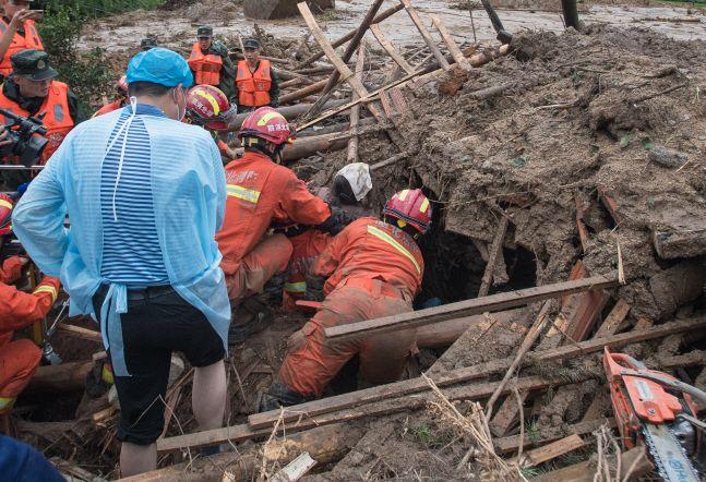 8일(현지시간) 중국 후베이성 황메이현에서 폭우로 산사태가 일어나 구조대원들이 잔해 속에서 한 할머니를 구조해 끌어내고 있다.ⓒ신화/뉴시스