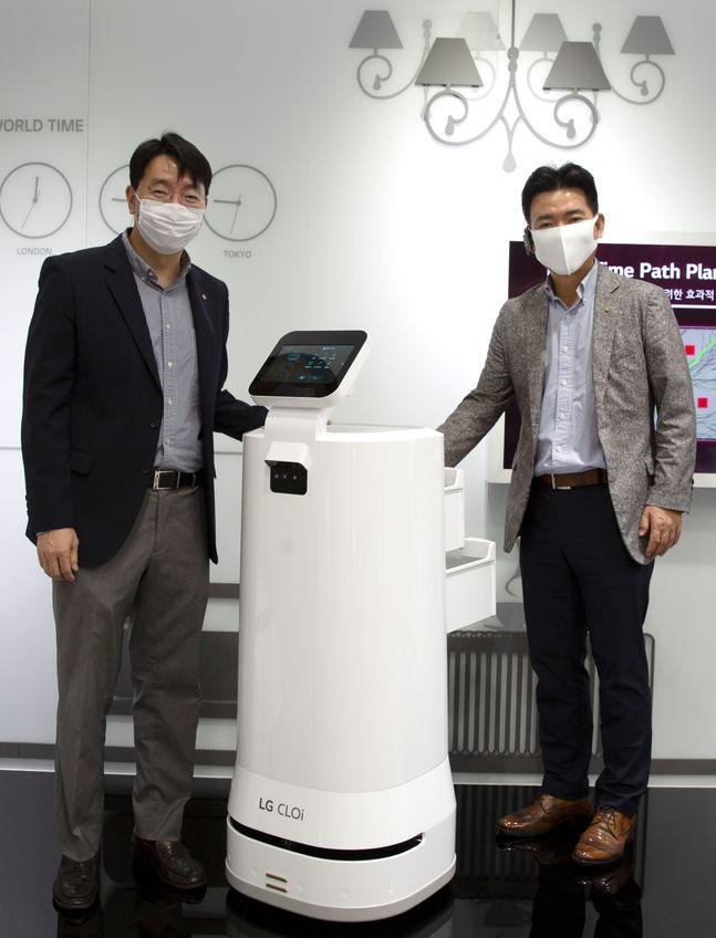 김성기 GS리테일 상무와 정원진 LG전자 상무가 배달 로봇과 함께 포즈를 취하고 있다.ⓒGS리테일