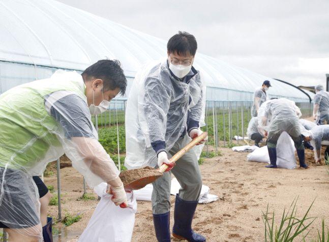 이재식(오른쪽) 농협 상호금융 대표이사가 6일 경기도 안성시 일죽면에서 호우피해 농가를 찾아 하우스 배수로 토사제거 작업을 하고 있다.ⓒ농협