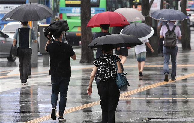 지난달 22일 오전 서울 종로구 광화문 거리에서 시민들이 우산을 쓴 채 발걸음을 옮기고 있다.(자료사진)ⓒ데일리안 홍금표 기자