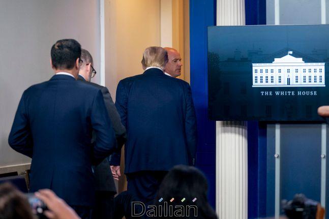 도널드 트럼프 미국 대통령이 10일(현지시각) 백악관 브리핑실에서 코로나19 브리핑 중 비밀경호국 경호팀으로부터 브리핑실을 떠나라는 요청을 받고 급히 방을 나가고 있다. ⓒAP/뉴시스