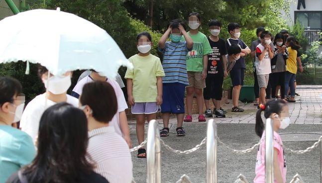 서울의 한 초등학교 임시 선별진료소에서 학생들이 검사를 받기 위해 길게 줄지어 서 있다.ⓒ연합뉴스