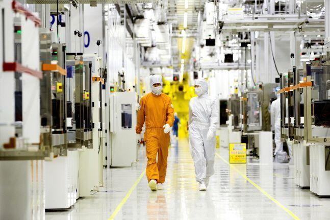 삼성전자 직원들이 클린룸 반도체 생산라인 사이를 걸어가고 있다.ⓒ삼성전자