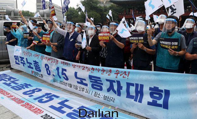 코로나19 예방을 위해 페이스 실드(얼굴 가리개)를 썼지만, 마스크를 제대로 착용하지 않은 전국민주노동조합총연맹 노조원들이 지난 15일 오후 서울 종로구 보신각 앞에서 기자회견 형식의 집회를 진행하고 있다. ⓒ뉴시스