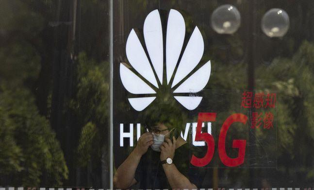 중국 베이징의 한 화웨이 매장에서 마스크를 착용한 직원이 통화를 하는 모습.ⓒ뉴시스