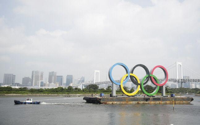 일본 도쿄 오다이바 해양공원 바지선에 설치됐던 2020 도쿄 올림픽&패럴림픽 오륜 조형물이 예인선에 이끌려 이동하고 있다.ⓒ뉴시스