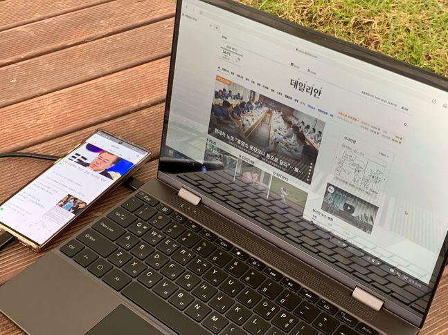 KT '플립북'을 삼성전자 스마트폰 '갤럭시노트10'과 연결해 웹서핑을 하는 모습.ⓒ데일리안 김은경 기자