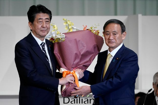 아베 신조(왼쪽) 일본 총리가 14일 도쿄의 한 호텔에서 열린 자민당 총재 선거에서 총재로 선출된 스가 요시히데 관방장관에게 꽃다발을 건네며 축하하고 있다. ⓒAP/뉴시스