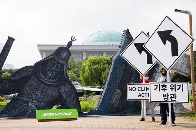 국제환경단체 그린피스가 서울의 주요 건물인 광화문, 남산서울타워, 이순신 장군 동상이 폭염으로 녹아내리는 가상 상황을 보여주는 퍼포먼스를 하고 있다. ⓒ그린피스