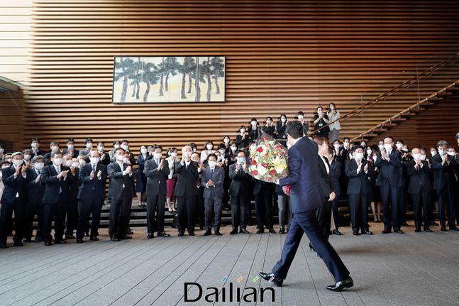 아베 신조 일본 총리가 16일 도쿄 총리실에서 떠나며 박수하는 직원들에게 손을 흔들며 인사하고 있다. ⓒAP/뉴시스
