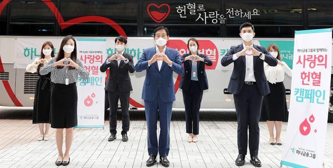 17일 하나금융지주 명동사옥 야외주차장에 마련된 헌혈버스 앞에서 김정태 하나금융 회장(가운데)이 헌혈 캠페인에 참여한 직원들과 함께 헌혈로 사랑을 나누자는 의미로