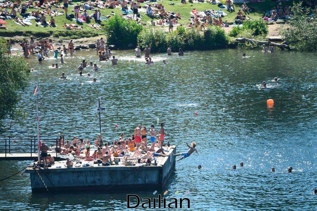 지난 8월 스웨덴 수도 스톡홀름의 랑홀멘섬에 모인 시민들이 일광욕, 수영 등을 즐기고 있는 모습 ⓒAP/뉴시스