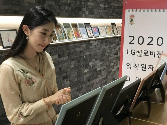 LG헬로비전 직원이 서울 마포구 상암동 사옥에 전시된 '자녀그림 콘테스트' 작품을 감상하고 있다.ⓒLG헬로비전