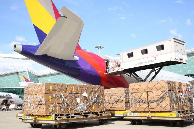아시아나항공 및 조업사 직원들이 24일 인천국제공항 제 1여객터미널에서 화물기로 개조한 A350 항공기 기내에 수출화물을 탑재하고 있다.ⓒ아시아나항공