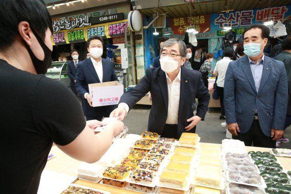 윤석헌(왼쪽) 금융감독원장이 9월 24일 서울 마포구 망원월드컵시장을 방문해 떡을 구매하고 있다. 사진 = 금융감독원