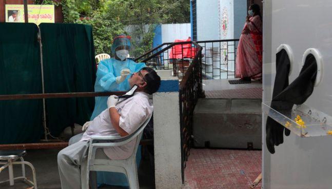 29일(현지시간) 인도 하이데라바드에서 한 보건 관계자가 주민들의 코로나19 검사를 하고 있다.ⓒAP/뉴시스