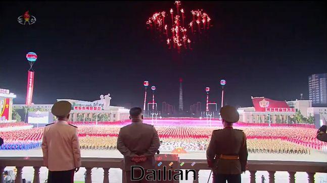 10일 북한 평양 김일성광장에서 대규모 열병식이 진행되고 있는 가운데 김정은 국무위원장(가운데)이 비행기 모양으로 추정되는 불꽃을 바라보고 있다. ⓒ조선중앙TV 갈무리