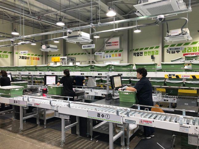 롯데마트 중계점에 설치된 온라인 배송 자동화 시설에서 근무자가 상품을 포장하고 있다.ⓒ롯데마트